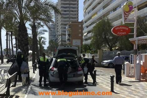 Los agentes guardan el material incautado en su coche.