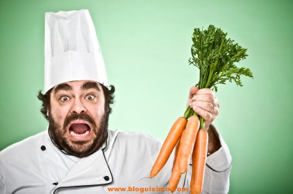 vegetarian cook chef with bunch of carrots on green backgrround